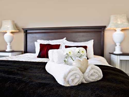folded white towels on a hotel bed